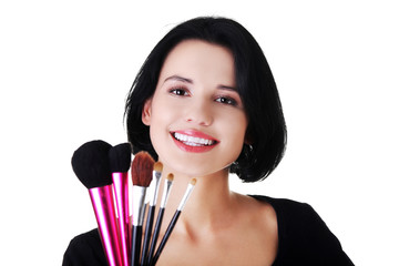 Happy woman with make up brushes