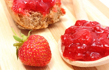 Fresh fruits and strawberry jam on wooden cutting board
