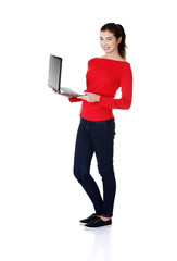 Full length student woman showing her laptop