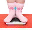 Overweight woman in funny socks standing on a weighing machine.
