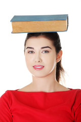 Worried young woman holding book on her head