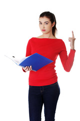Pretty female student holding notebook pointing up