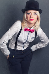 beautiful young woman wearing tophat, bow-tie and braces against