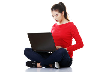 Pensive woman sitting cross-legged with laptop