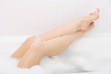 Beautiful female legs in bathtub with foam