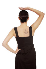 Back view of a woman in dress with coffee tattoo