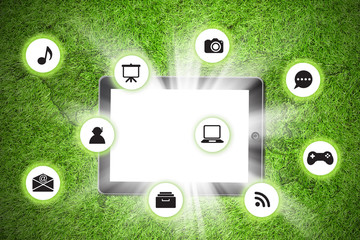 Tablet pc on with icon on grass background