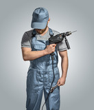 construction worker builder with drill and wrench on the isolate