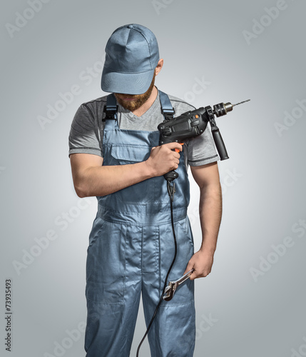 construction worker builder with drill and wrench on the isolate - 73935493