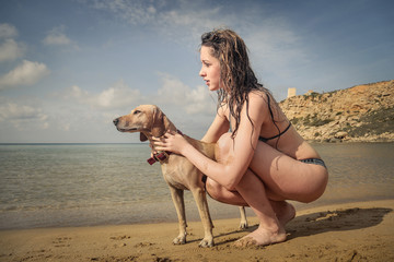 A girl and her dog playing at the beach