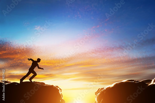 Man running fast to jump over precipice between two mountains - 73937402
