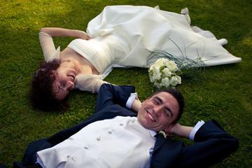 sposi felici sdraiati su prato verde
