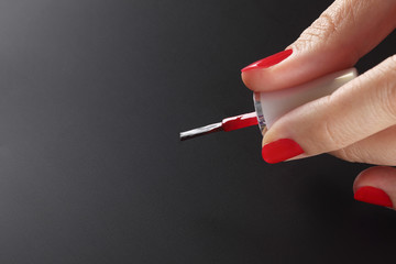 Red nail polish brush in woman hand