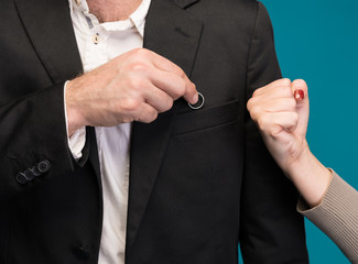 Man hiding wedding ring, woman showing him a fist