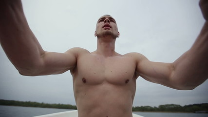Muscular strong man row of boat floating with oars slow motion