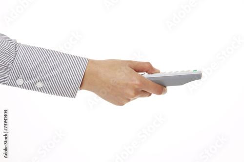 canvas print picture Hand hält graue Fernbedienung, Seitenansicht