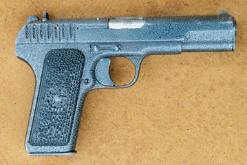 Soviet Tokarev TT pistol on canvas covered with rain drops.