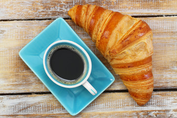 Coffee and croissant on rustic wooden surface