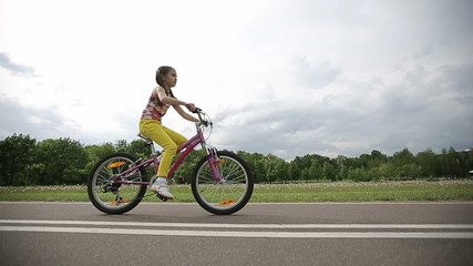 Little girl cycling in park on a pink bike in slow motion