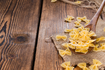 Raw Farfalle (on wooden background)
