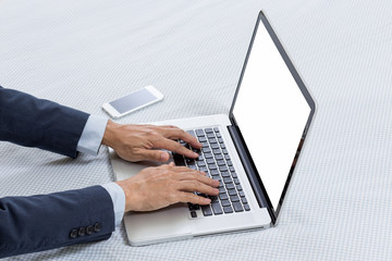 Laptop computer on bed with businessman hands