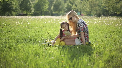 Mother and daughter sitting on the grass read book at sunset