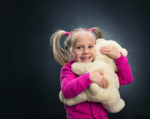 Small cute girl holds toy bear