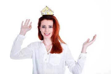 Junge rothaarige Frau balanciert Miniatur Haus auf Kopf