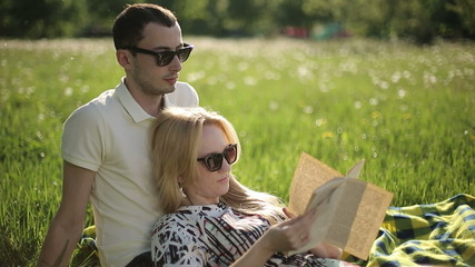 Loving couple in sunglasses at sunset read book on field