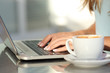 Woman hands typing in a laptop in a coffee shop - 73946661