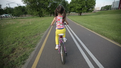 Little girl cycling in park on a pink bike sequence