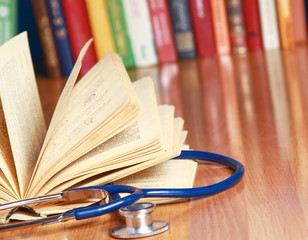 A stethoscope is lying with a book on the desk against books.