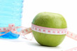 A green apple, a bottle of water and a measuring tape
