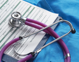 A stethoscope and RX prescription are lying on a medical uniform