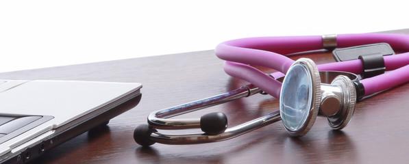 A violet stethoscope near a laptop .