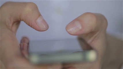 Close up of woman white dress fingers typing on her smartphone
