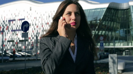 Businesswoman chatting on cellphone and smiling, steadycam shot