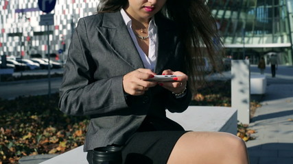 Businesswoman sitting outside the building and texting,steadycam