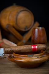 Cigars with barrel of rum on table