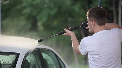 Man in a white t-shirt washes white car Slow motion