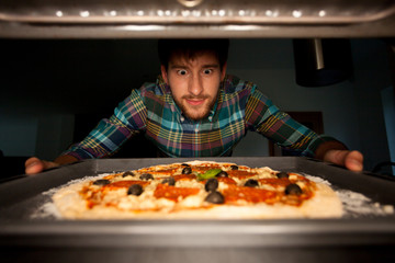Man taking pizza from oven