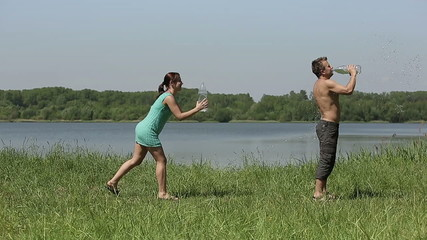 Young couple battle water of plastic bottles slow motion