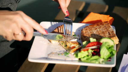 Woman cutting brushetta by using cutlery outside the cafe