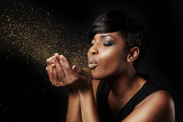 black woman blowing golden dust