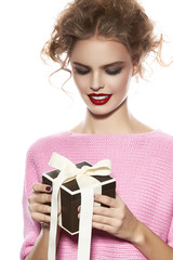 Beautiful woman with evening make-up takes box with present