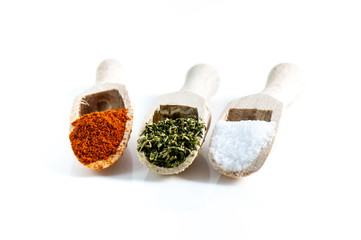 Spices in wooden spoons on a white background.