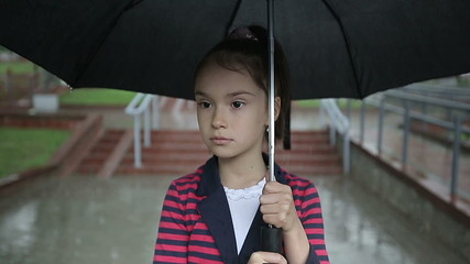 Close up child girl in the rain under an umbrella slow motion.