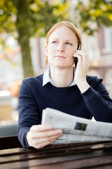 Businesswoman with Newspaper Calling by Phone