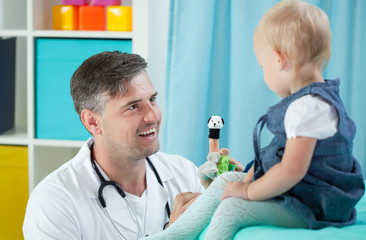 Smiling pediatrician and his little patient