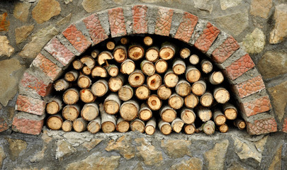 Pile of dry chopped firewood logs inside a brick oven.
